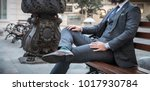 suited man sitting on bench... | Shutterstock . vector #1017930784
