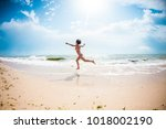 a girl is jumping on the beach... | Shutterstock . vector #1018002190