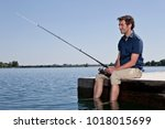 man fishing on dock | Shutterstock . vector #1018015699