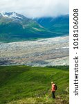 Small photo of Woman hiking in the mountains. Enjoying the view. Active life. Alaska range. Glacier.