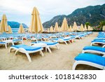 sun loungers on a beach in... | Shutterstock . vector #1018142830
