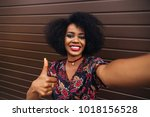 Pretty afro-american girl showing a thumb up while taking a selfie on cellphone. Dressed in colorful blouse, with lush hairstyle.