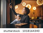 woman in cafe doing selfie and... | Shutterstock . vector #1018164340
