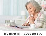 happy aged woman  reading... | Shutterstock . vector #1018185670