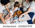 pregnant family looking through ... | Shutterstock . vector #1018267549