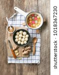 """Small photo of Flat lay Chinese new year food """"tang yuan"""" plain glutinous rice ball hot soup dessert on rustic wooden kitchen counter top."""