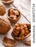 Small photo of Walnut. Walnut kernels and whole walnuts on rustic old table. Healthy food concept