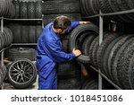 male mechanic holding car tire... | Shutterstock . vector #1018451086