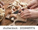 woman cutting mushrooms on... | Shutterstock . vector #1018485976