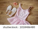 Stock photo pink dress for dances and a cane on a wooden background 1018486480
