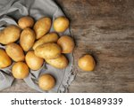 fresh raw potatoes on wooden... | Shutterstock . vector #1018489339