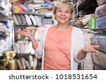 Small photo of Adult female housewife buyer choosing textile goods in the store