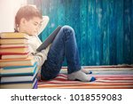 eight years old child reading a ... | Shutterstock . vector #1018559083