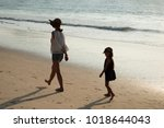 mother and daughter walking on... | Shutterstock . vector #1018644043
