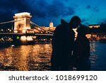 Small photo of Romantic silhouettes portrait of the loving couple almost kissing at the background of the shining Chain Bridge on River Danube in Budapest, Hungary at night.