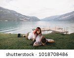 beautiful young couple in love looking at each other while lying on grass near mountain lake in Bern, Switzerland