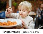 cute toddler boy eating pasta... | Shutterstock . vector #1018711549