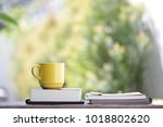 yellow cup with books on wooden ... | Shutterstock . vector #1018802620