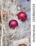 Small photo of Festive Christmas claret balls on the branches of a white snowy tree