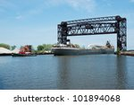 A small tugboat guides the Great Lakes bulk freight ship Cuyahoga stern first under the Norfolk Southern Railroad drawbridge that spans the mouth of the Cuyahoga River in Cleveland, Ohio - stock photo