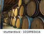 stack of oak barrels in cellar... | Shutterstock . vector #1018983616