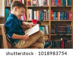 boy reading a book sitting on a ... | Shutterstock . vector #1018983754