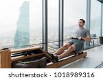 man working out on row machine...   Shutterstock . vector #1018989316