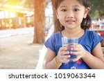 portrait of asian kid drinking... | Shutterstock . vector #1019063344
