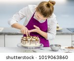 woman decorating chocolate cake ...   Shutterstock . vector #1019063860
