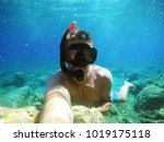 Small photo of Handsome young adventuristic scuba diver man taking a selfie with an action camera in the turquoise sea.