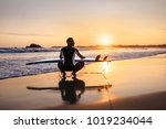 surfer with surfboard sits on... | Shutterstock . vector #1019234044