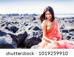 Stock photo beautiful indian woman wearing saree sitting on a shore in mumbai 1019259910