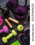 Small photo of Top view image of a pair of women sport shoes, sport bra, dumbbells, kettle-bell, fitness gum, smart phone with headphones, jumping rope, wristband and an apple aligned on a dark wooden background