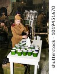 Small photo of Filling juice on iron mugs. St. Petersburg, Russia - 7 May, 2017. Visitor in the exhibition pavilion of the Patriotic Association of Lenrezerv.