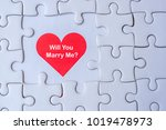 Small photo of white jigsaw puzzle piece with Red heart and Will you Marry me? Wording. Love and Happy Valentine's day concepts