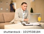 businessman working on couch | Shutterstock . vector #1019538184