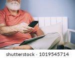 senior man holding remote...   Shutterstock . vector #1019545714