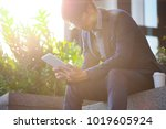 young businessman sits on steps ...   Shutterstock . vector #1019605924