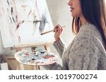 Young woman artist painting at...
