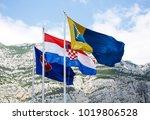 Small photo of MAKARSKA,CROATIA-18 JUNE,2017: National flag of Croatia and region of Dalmatia flatter in wind on high poles