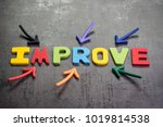 Small photo of Multiple arrow pointing to colorful alphabet word IMPROVE at the center on dark black cement wall background, self improvement motivation concept.
