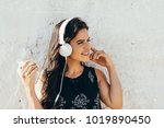 young woman listening to music... | Shutterstock . vector #1019890450