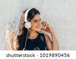 young woman listening to music... | Shutterstock . vector #1019890456
