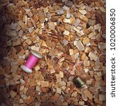 Small photo of pink coil of thread and an iron thimble lying on wood chips of alder