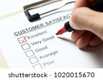 Small photo of Customer satisfaction survey form on clipboard with red pen