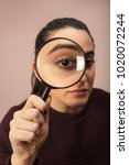 Small photo of Woman searching for clues or conducting an investigation or search peering through a handheld magnifying glass , what makes his eye seem bigger