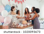 Stock photo women toasting with juices at baby shower party group of friends at baby shower party having 1020093673
