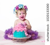 Small photo of Cute happy baby girl with blue eyes is tasting the cake and purple butter icing on her sticky fingers from her first birthday cake smash while sitting on a white background