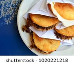 Small photo of Arepas filled with shredded meat and cheese.Venezuelan typical dish. Traditional Colombian food.Arepa is a popular breakfast and snack in Latin American countries.Top view.Selective focus.