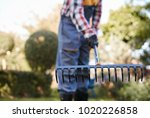 defocused man raking leaves at... | Shutterstock . vector #1020226858